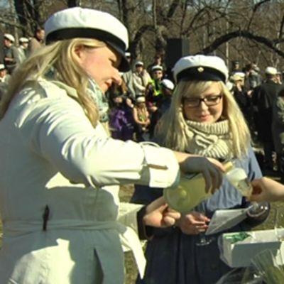 Kaksi ylioppilaslakkista neitoa tarjoaa kuohuviiniä kahdelle järjestysmiehelle.