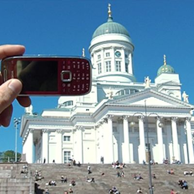 Miehen käsi pitää matkapuhelinta ottaakseen valokuvan Helsingin Tuomiokirkosta.