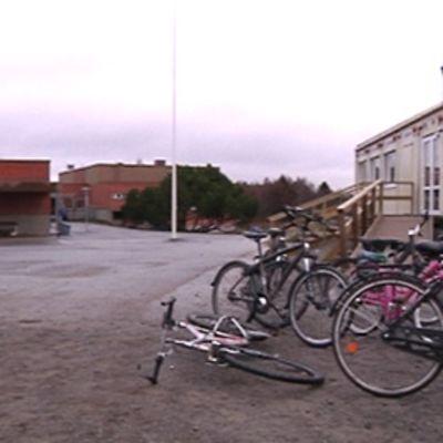 Kuvassa Isokylän koulun pihapiiri, oikealla parakkikoulu ja taustalla päärakennus, etualalla polkupyöriä
