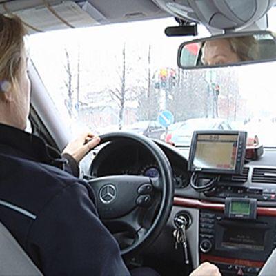 Taksinkuljettaja ajaa taksia.