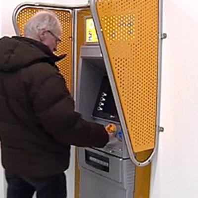 Mies käteisautomaatilla
