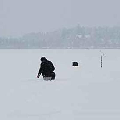 Mies pilkkii järvellä lumituiskussa.
