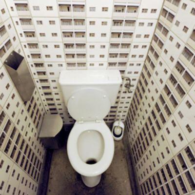 Illuusiomainen kuva, jossa on optisesti luotu harha jättimäisestä vessanpöntöstä kerrostalojen keskellä.