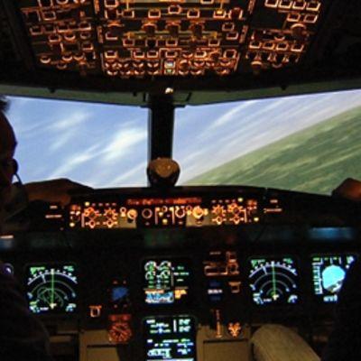 """Kaksi lentäjää lentosimulaattorin hämärässä ohjaamossa. Ohjaamo kallistuu oikealle. Ohjaamon """"ikkunoista"""" näkyy maisema päivänvalossa."""