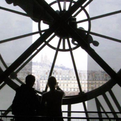 Kaksi henkilöä seisoo valtavan kellon alla d'Orsayn museossa Pariisissa.