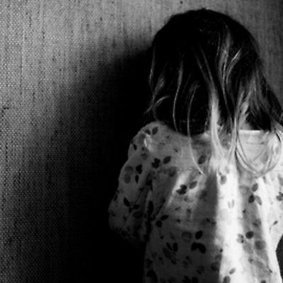 Lapsi seisoo seinänä vieressä kasvot seinää vasten