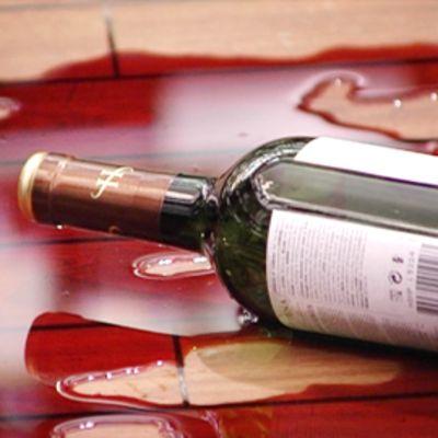 Punaviiniä ja rikkoutunut viinipullo lattialla.