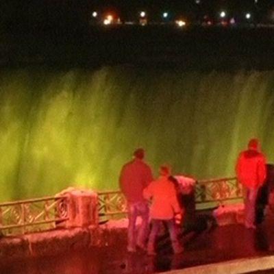 Ihmiset kävelevät valaistujen Niagaran putousten ohitse.