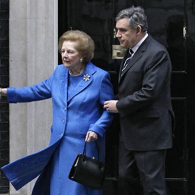 Gordon Brown pitää kiinni Margaret Thatcheristä, joka pitää toisella kädellään kiinni rautaportista.