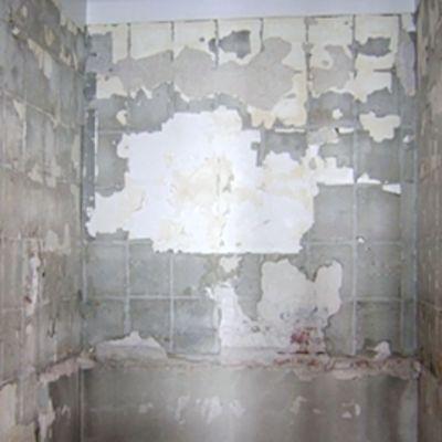 Mies katsoo remontissa olevaa kylpyhuonetta.