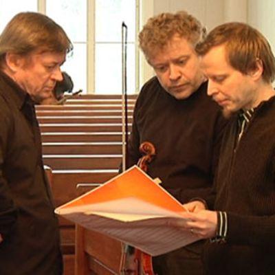 Kapellimestari Juha Kangas ja konserttimestari Reijo Tunkkari tarkastelevat partituuria yhdessä säveltäjä Veli-Matti Puumalan kanssa.