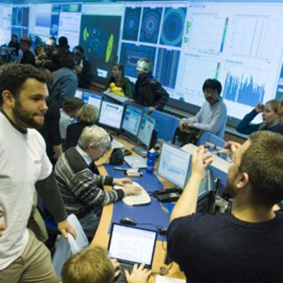 Tutkijoita CERNin kontrollikeskuksessa käynnistämässä suurta hiukkaskiihdytintä.