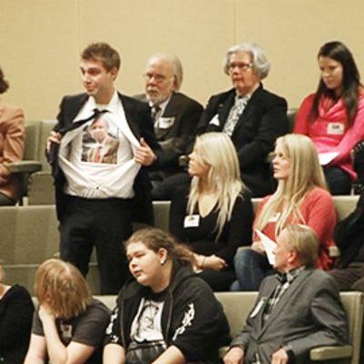 Henkilö häiriköi eduskunnan istunnossa avaamalla paitansa torstaina 17. marraskuuta 2011.