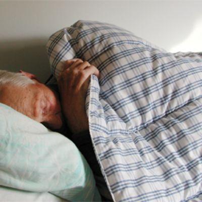 Vanhus nukkuu peiton alla