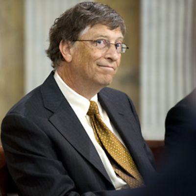 Bill Gates hymyilee kahden etualalla olevan epäselvän ihmishahmon välistä.