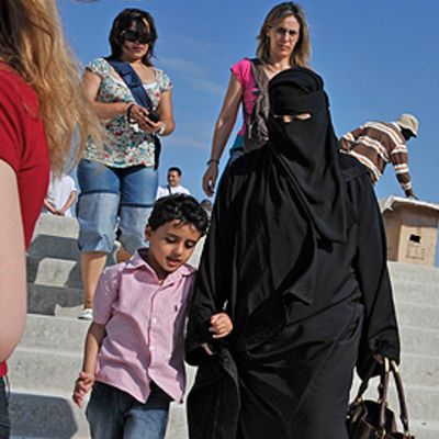 Niqabiin pukeutunut nainen kävelee lapsen kanssa portailla.