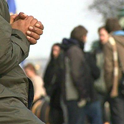 Keräjäläinen istuu kadulla kämmenet vastakkain. Ihmisiä keskustelee taustalla keskenään.