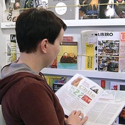 Nainen lukemassa lehteä