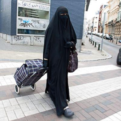 Hunnutettu nainen kävelee kadulla