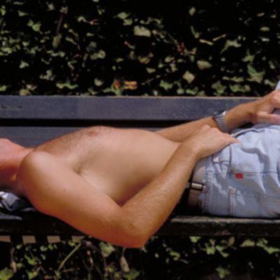 Mies ottaa aurinkoa puistonpenkillä.