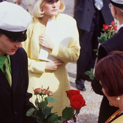 Äiti ojentamassa ruusua pojalleen ylippilasjuhlissa
