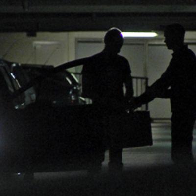 Kaksi ihmistä juttelee keskenään hämärässä parkkihallissa. Oikealla oleva mies ottaa salkun vastaan.