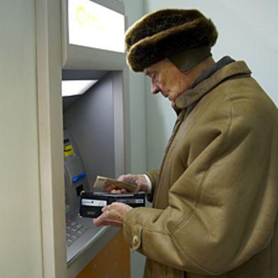 Eläkeläinen pankkiautomaatilla