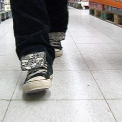 Nuori kävelee kaupan olutosastolla.