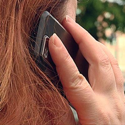 Nainen puhuu kännykkään.