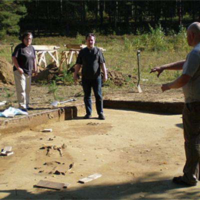 Arkeologeja kauvauksilla Keskellä hauta, jonka takana näkyy muiden hautojen jättämiä värjäymiä.