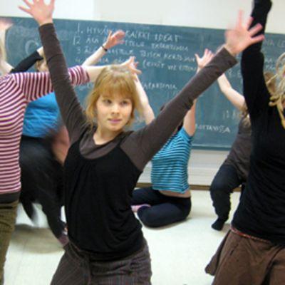 Joukko lukiolaistyttöjä harjoittelee näytelmää.