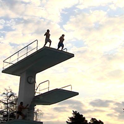 Pojat hyppäävät Uimastadionin hyppytornista.