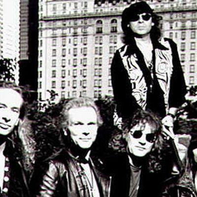 The Scorpions -yhtyeen jäsenet Ralph Rieckermann, Rudolf Schenker, Herman Rarebell, Klaus Meine ja Matthias Jabs ulkona kaupunkimaisemassa auringonpaisteessa. Mustavalkokuva.
