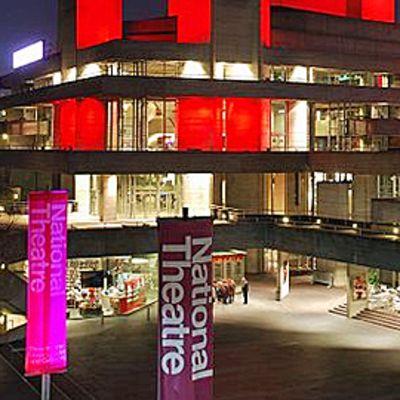 Yökuva National Theatren modernista rakennuksesta, edessä punaisia ja sinisiä lippuja, joissa teatterin nimi.