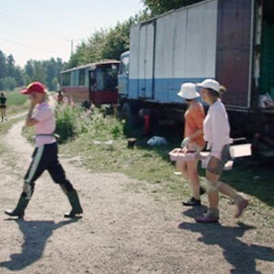 Mansikanpoimijat kantavat koreja marjatilalla.