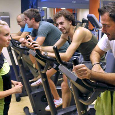 Neljä miestä polkee kuntopyörillä,  nuori naisohjaaja katselee.
