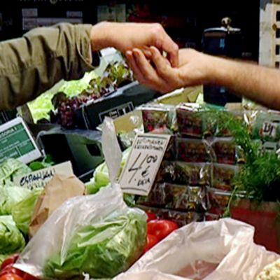 Mies maksaa käteisellä Hakaniemen kauppahallissa.