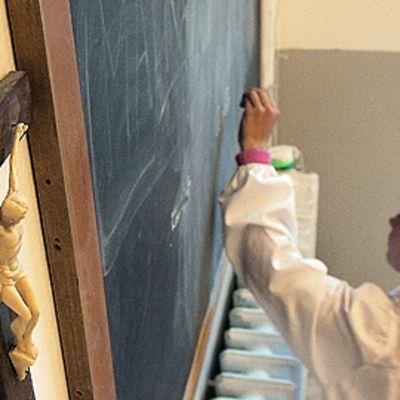 Italialaistyttö kirjoittaa liitutauluun, jonka viereen seinälle on kiinnitetty krusifiksi.