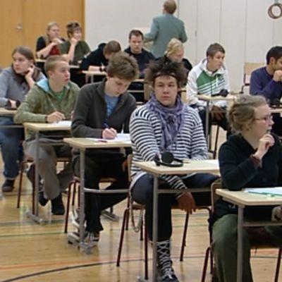 Abiturientteja istuu koulun juhlasalissa ennen ylioppilaskokeen alkua.