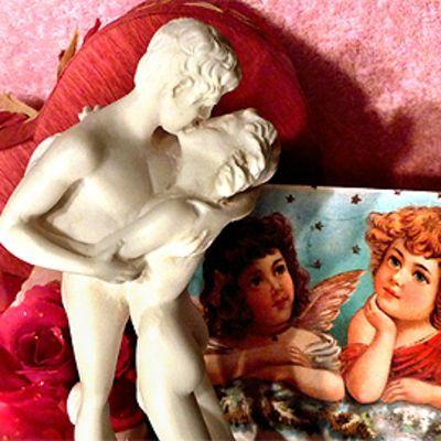 Valkoinen pikkupatsas suutelevasta parista, taustalla punainen sydän ja ruusu sekä enkelikortti.