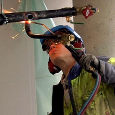 Rakennusmies hitsaa pillihitsillä vesiputkia rakennustyömaalla.