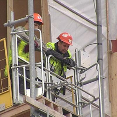 Kaksi rakennusmiestä nojaa kaiteeseen rakennuksen yläkerroksessa ja katsoo alas.