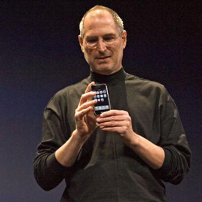 Steve Jobs kädessään iPhone, taustalla valkoinen Applen logo.