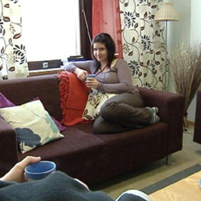 Ohjaaja Henna Kirvesmäki istumassa sohvalla.