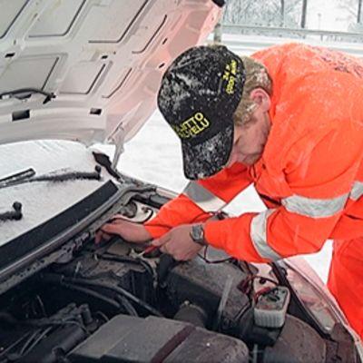 Autoliiton Tiepalvelun mies tarkastaa auton sähköjä