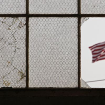 Guantánamon erään parakin kuusiosaisen ikkunan läpi kuvattu maisemanäkymä. Vasen lasi on rikkoutunut, oikeimmaisin lasi on kokonaan pois. Avonaisesta ikkunanäkymästä näkyy Yhdysvaltain lippu.