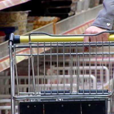 Mies työntää ostoskärryjä kaupassa.