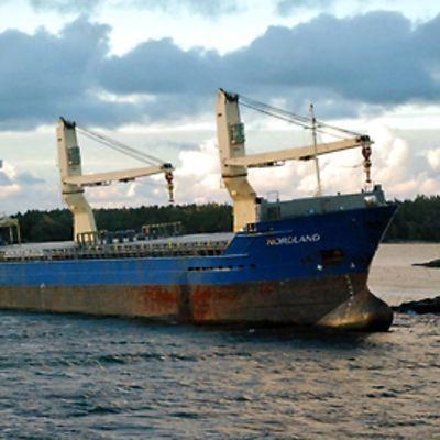 Nordland-laiva on ajanut karille. Aamuaurinko nousee taustalla.