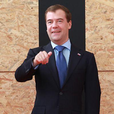Vasemmalla oleva Rasmussen nauraa, kun Medvedev viittoloi käsillään.