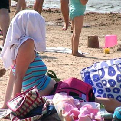 Nainen rannalla pyyhe päässään